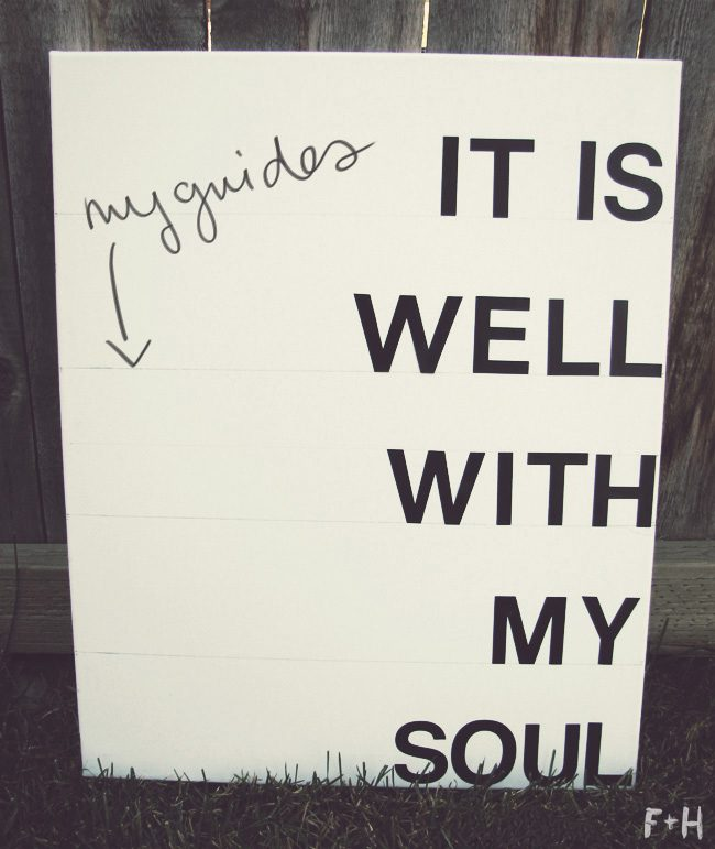 "white canvas with black letters reading ""it is well with my soul"" leaned on a fence outside on grass"