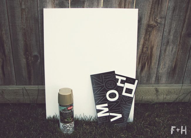 white canvas with can of gold spray paint and vinyl stick on letters  all sitting on grass against a fence