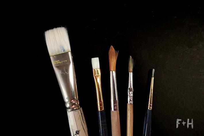 close up of paintbrushes on black background