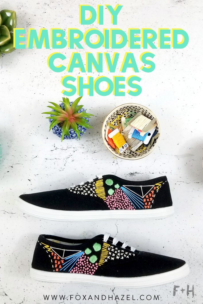 embroidered black canvas sneakers on white desk