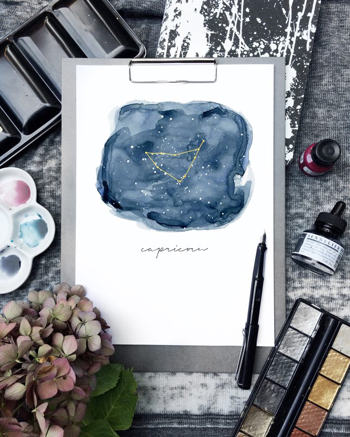 zodiac sign art on clipboard surrounded by art supplies