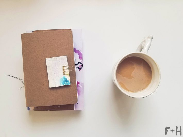 coffee mug and journal on white desk
