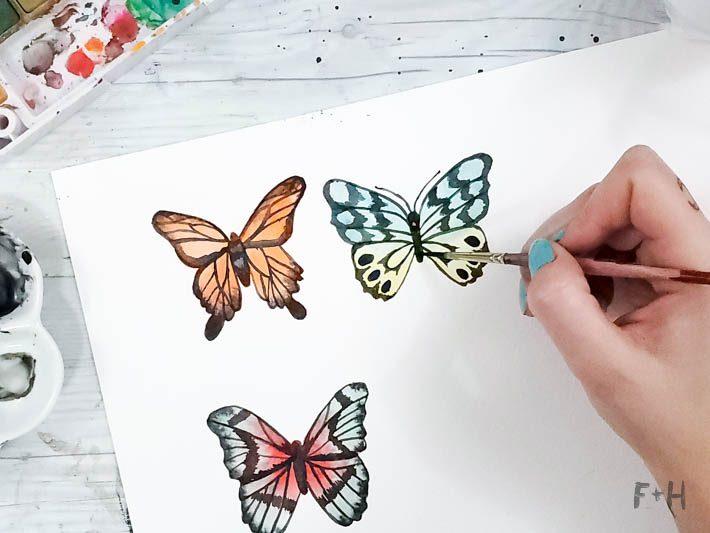 watercolor butterflies on white paper on desk