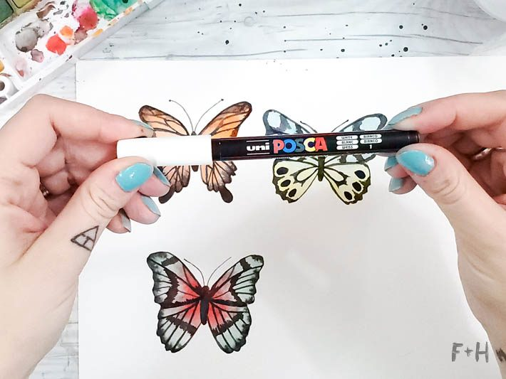 white paint marker in hands being held above watercolor butterfly painting
