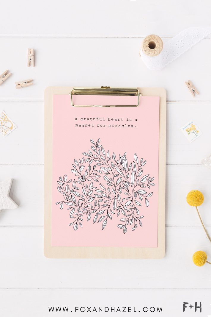 pink gratitude print on clipboard on white desk