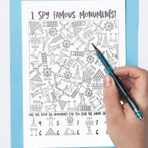 famous monuments i spy printable on blue clipboard with person's hand holding a pencil