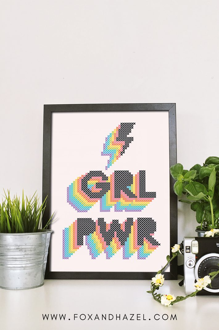 "Framed cross stitch inspired art print that reads ""GRL PWR"" in rainbow text. Sitting on a desk with plants and an old camera."