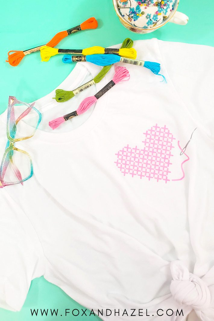 cross-stitch heart design on white t-shirt on green background surrounded by sewing notions