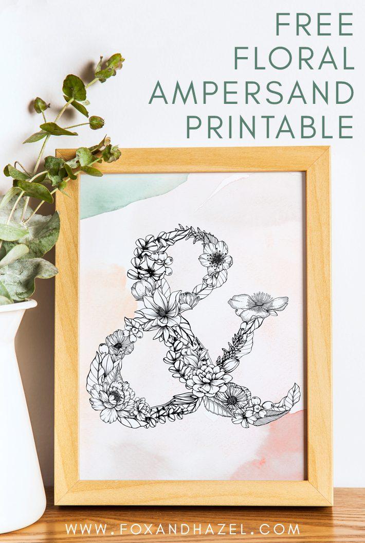 framed print of a floral ampersand design in wooden frame, sitting on desk with a vase of eucalyptus leaves