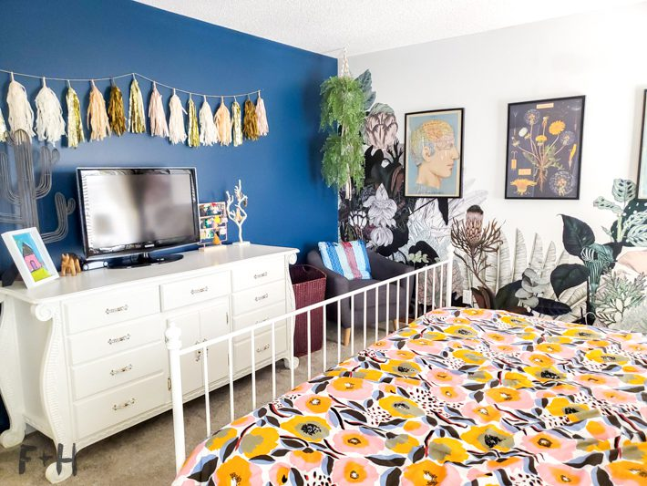 A decorated bedroom with a white dresser against a blue wall, adjacent to a jungle wallpaper mural. In the foreground is a colorful floral bedspread.