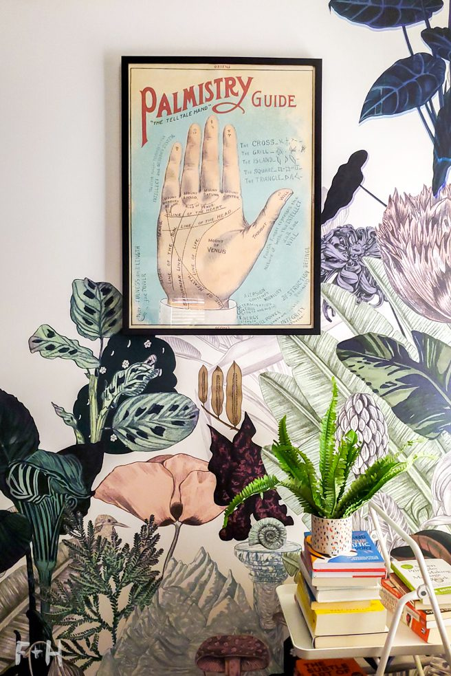 A wall with a jungle print wallpaper on it, with a black framed poster of a palmistry hand. In the lower corner is a stack of books with a plant on top.