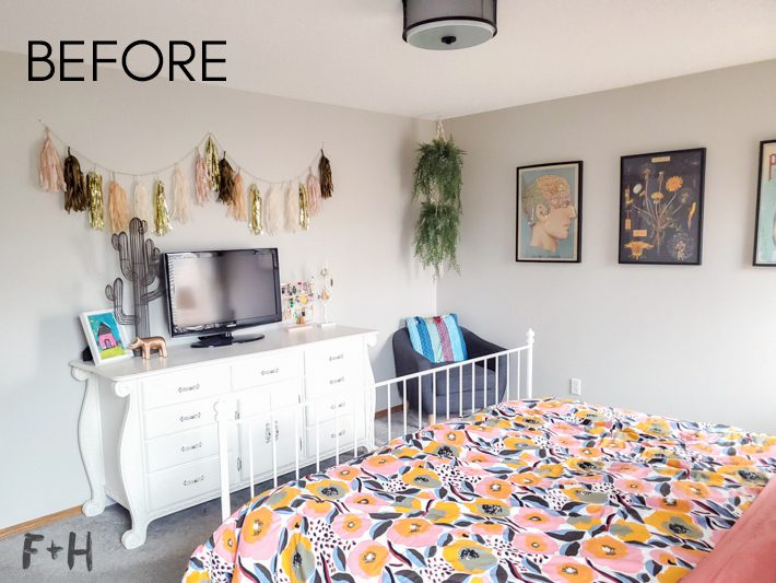 A decorated bedroom with a white dresser against a grey wall. Adjacent wall has posters in black frames hanging. In the foreground is a colorful floral bedspread.