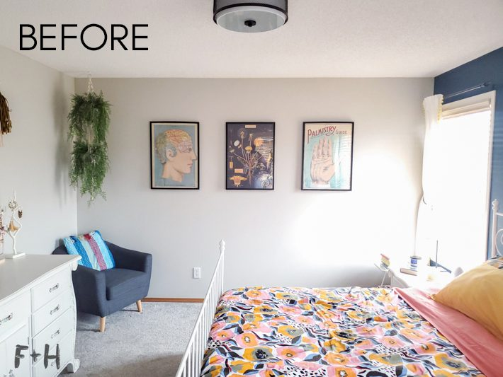 A decorated bedroom with posters in black frames hanging on the far wall. In the foreground is a colorful floral bedspread.