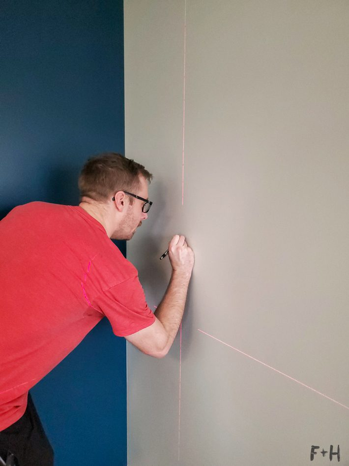 A man in a red shirt is marking a wall using a laser level.
