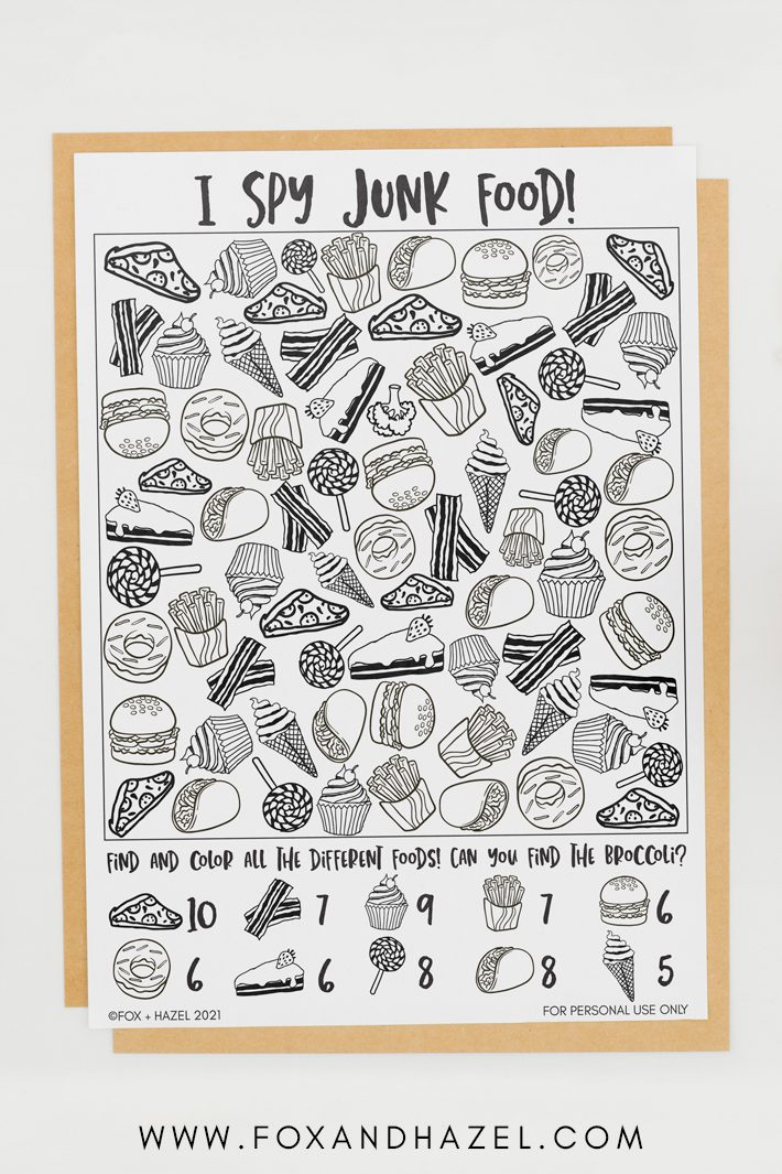 A junk food I spy printable sheet laying on top of brown paper on a white desktop