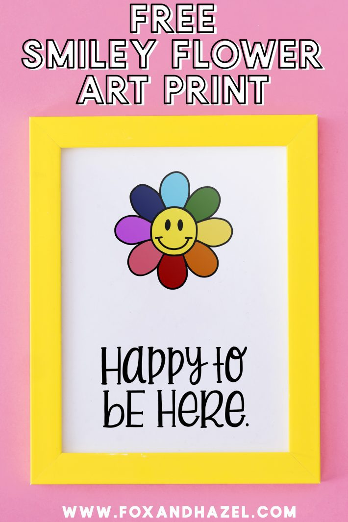 """free smiley flower art print in yellow frame with words """"happy to be here"""" on a pink background"""