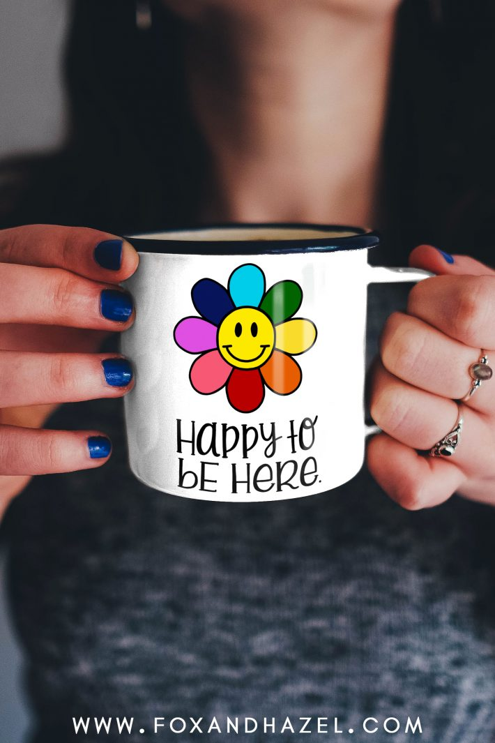 """woman holding a smiley flower coffee mug with words """"happy to be here"""""""