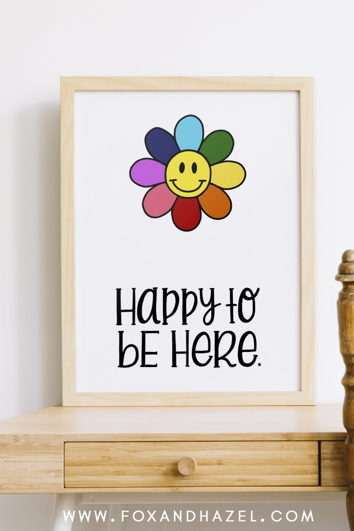 """free smiley flower art print in wood frame with words """"happy to be here"""" sitting on a wood desk."""